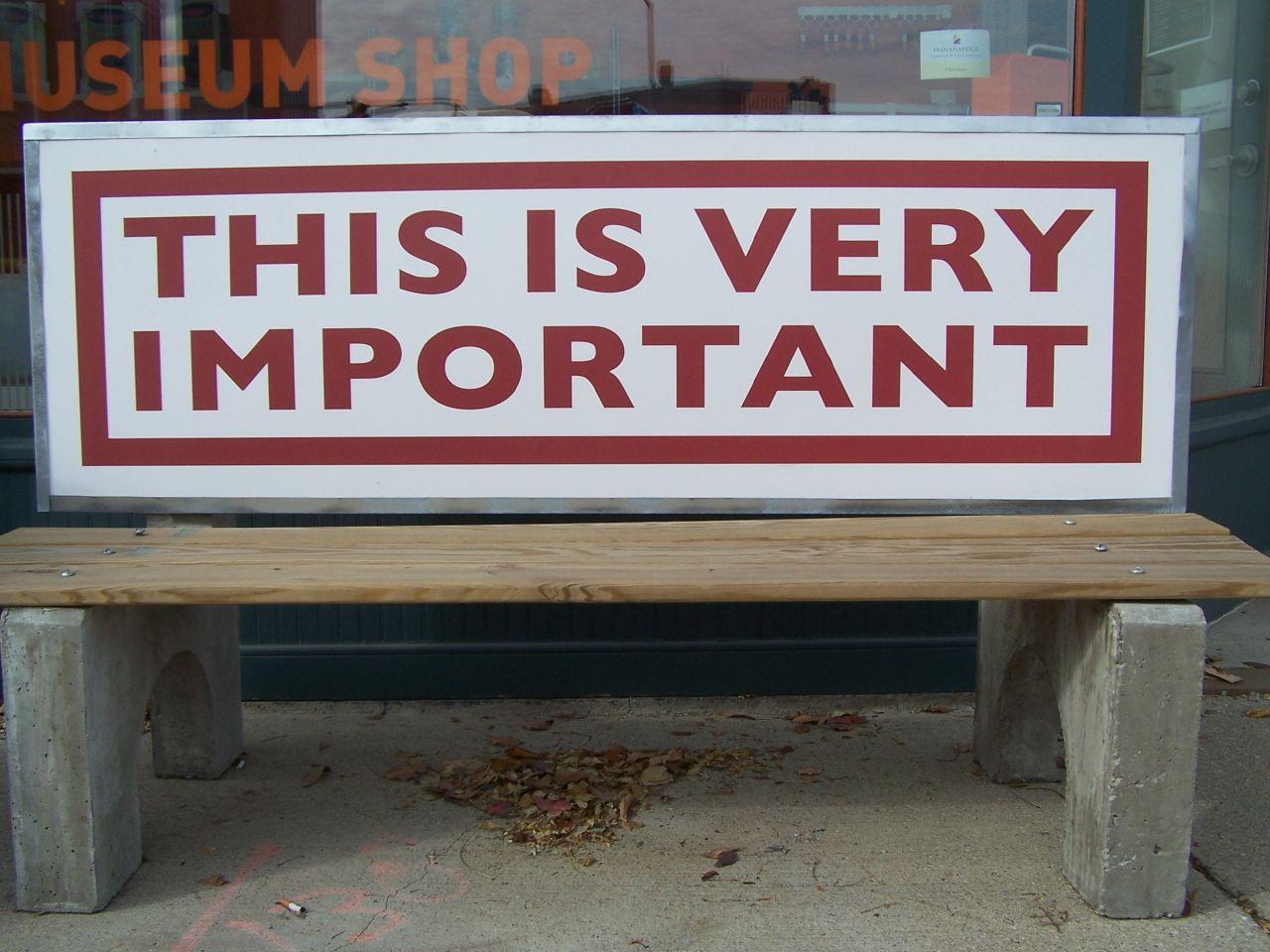 Ein großes Schild auf einer Sitzbank, das auf eine wichtige Sache hinweist.