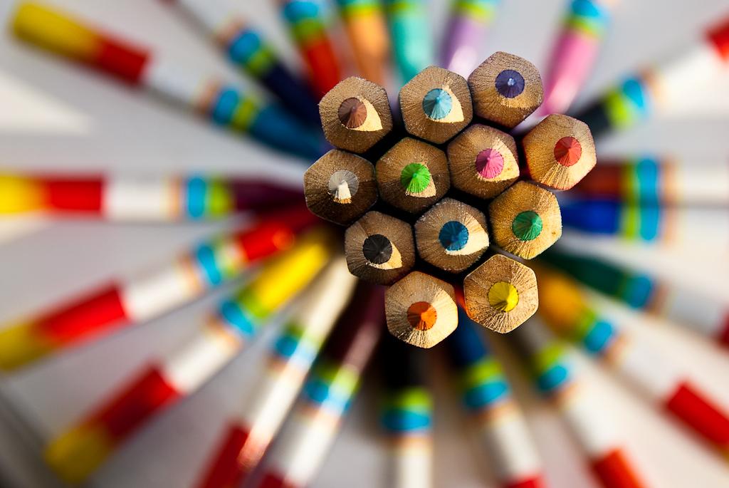Nahaufnahme von Buntstiften, die in Richtung des Betrachters zeigen. Im Hintergrund sind noch weitere Stifte zu erkennen.