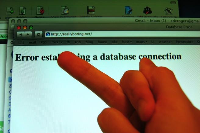 Foto eines augestreckten Mittelfingers, der auf eine Website zeigt, die einen Datenbankfehler ausgibt.