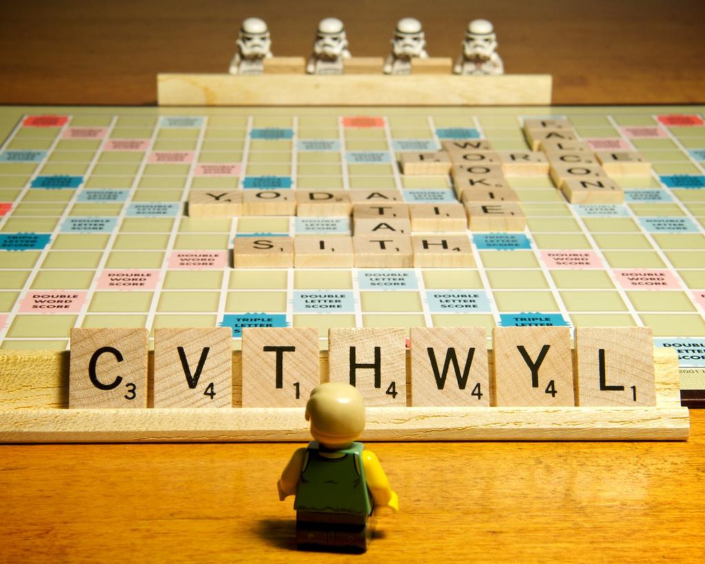 """Bild des Spiels """"Scrabble"""" mit einem Lego-Männchen im Vordergrund und Klon-Kriefern aus Starwars im Hintergrund"""