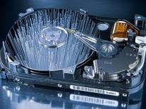 Eine aufgeschraubte Festplatte, deren spiegelnde Flächen die Enden von Glasfasern reflektieren