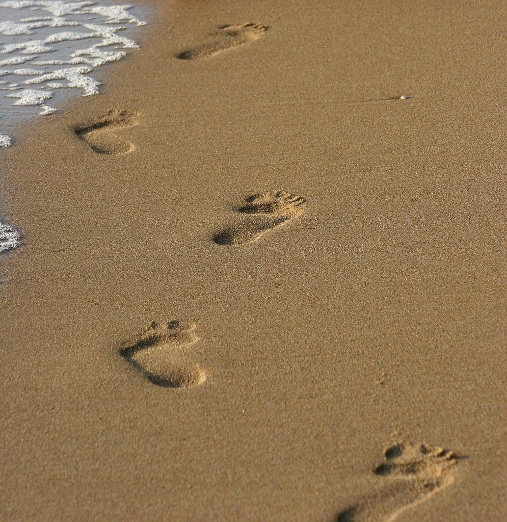 Fußspuren im Sand, auf der linken Seite sieht man die Gischt des Meeres