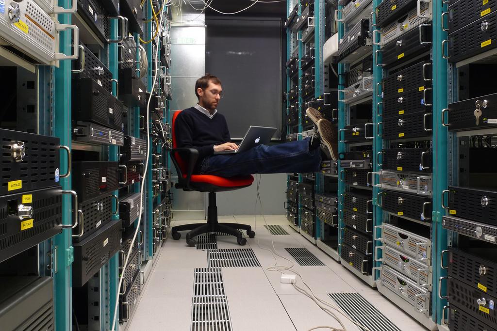 Ein Mitarbeiter eines Datacenters bei der Arbeit zwischen zwei Server-Reihen.