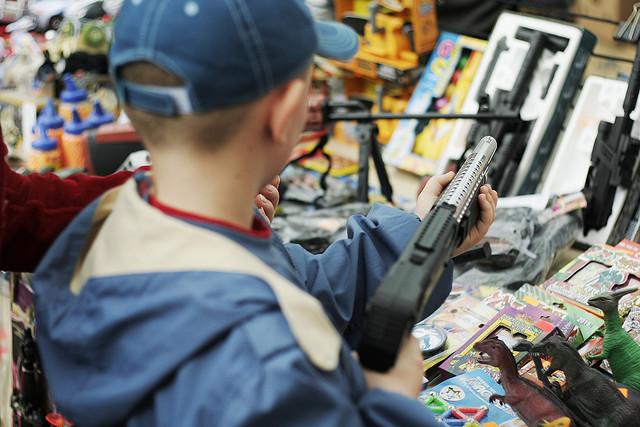 Ein Kind mit einer Spielzeugwaffe in der Hand. Dahinter sind noch weitere Spielzeugwaffen zu erkennen.
