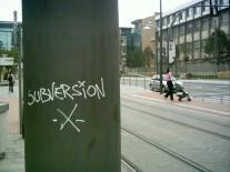 Eine Säule inmitten eine Stadt mit der Aufschrift Subversión. Dahinter sind Gleise erkennbar.