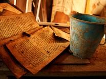 Ein altes, verwittertes Buch neben einem ebenso altertümlich wirkenden Eimer.