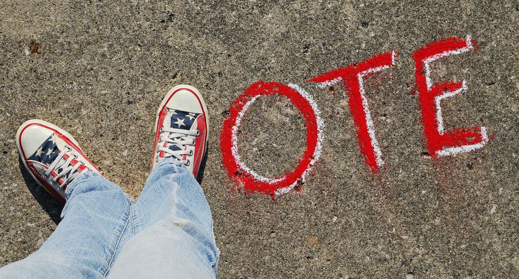 Das Wort Vote, welches auf eine Straße gemalt wurde und dessen erster Buchstabe aus Füßen gebildet wird.
