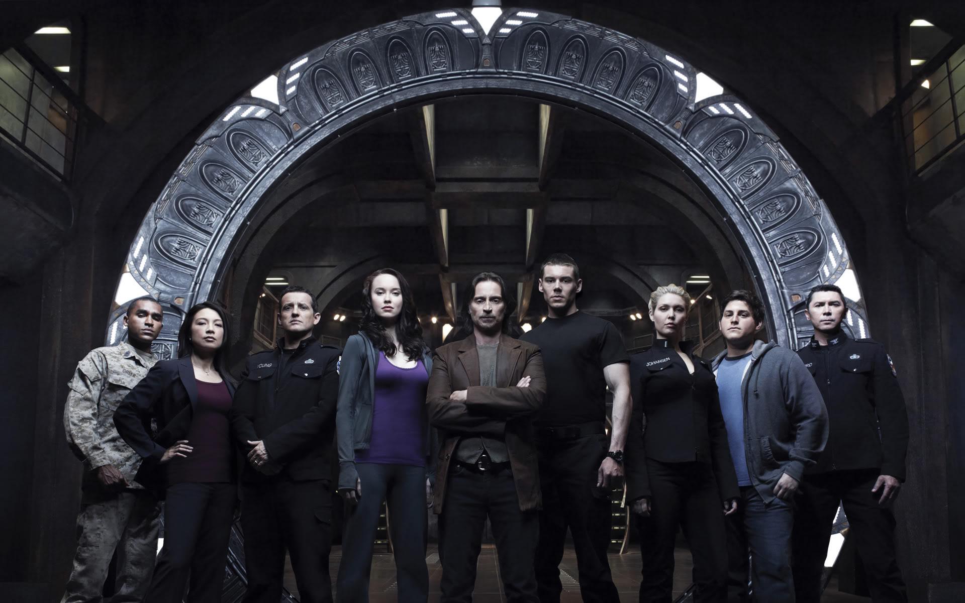 Schauspieler der Serie Stargate Universe vor dem Stargate auf dem Raumschiff Destiny.