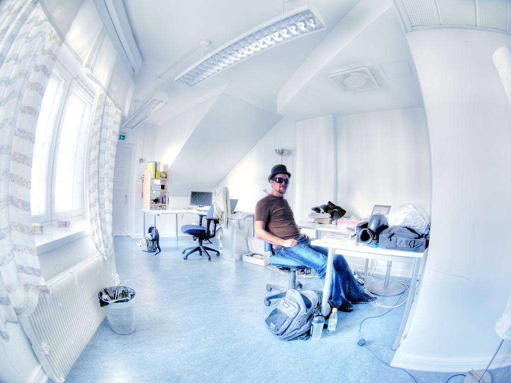 Futuristisches, minimal und hell eingerichtetes Büro mit einem Mitarbeiter an seinem Schreibtisch.