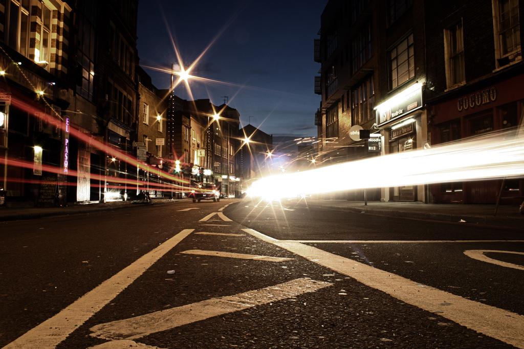 Langzeitaufnahme einer Straße mit vorbeifahrenden Autos, deren Scheinwerfer lange Lichtspuren ziehen.