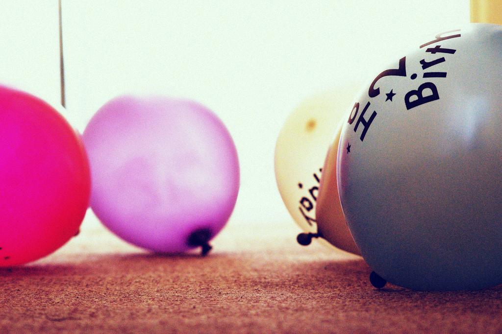 Stark im Farbton angepasstes Bild von Luftballons auf einem Tisch vor einem hellen Hintergrund.
