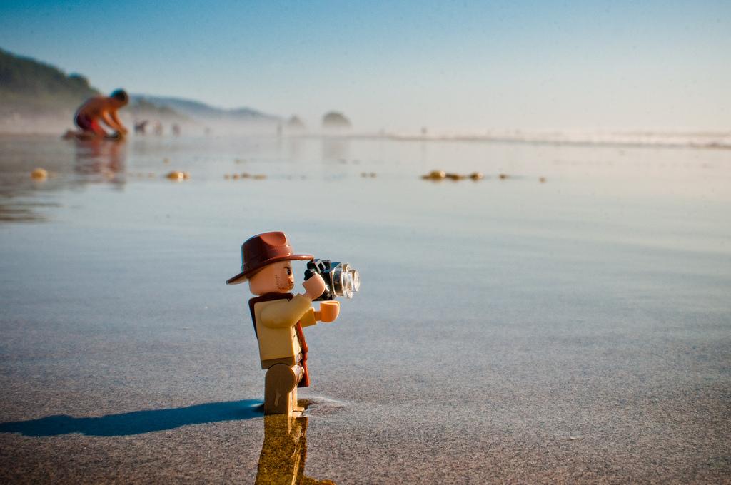 Indiana Jones als Lego-Figur am Strand mit einer Kamera in der Hand