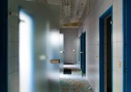 Foto eines Gangs, der von Glasscherben übersät ist und dessen abzweigende Glastüren offen stehen