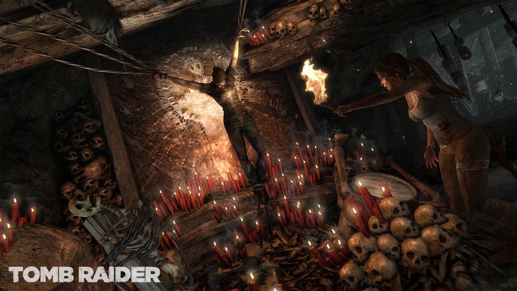 Screenshot aus Tomb Raider, der einen an Ketten hängenden Menschen zeigt, umgeben von Kerzen und Totenköpfen.