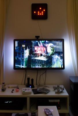 Foto meines Fernsehers und der dazugehörigen Technik und meiner Binäruhr. Einem unverkennbaren Gadget eines Nerds.