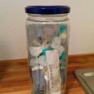 Einmachglas gefüllt mit leeren Spritzen und Nadeln.